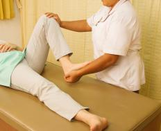 therapist-with-hand-on-womans-knee-on-cot